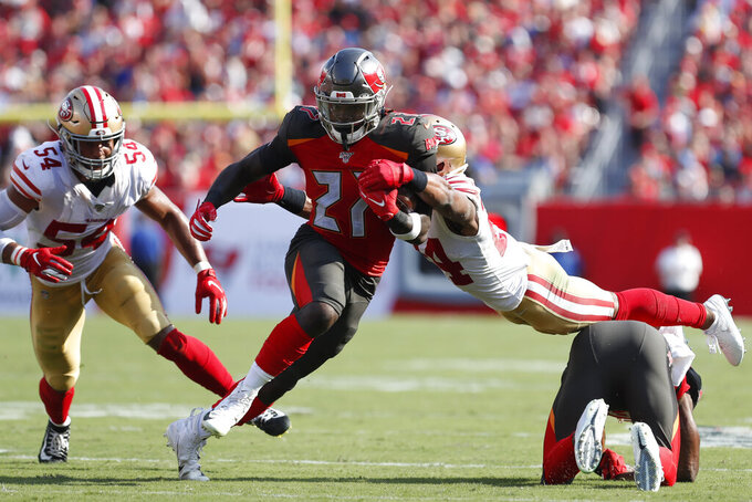 Tampa Bay Buccaneers running back Ronald Jones II (27) is caught up by San Francisco 49ers defensive back K'Waun Williams (24) during the first half an NFL football game, Sunday, Sept. 8, 2019, in Tampa, Fla. (AP Photo/Mark LoMoglio)