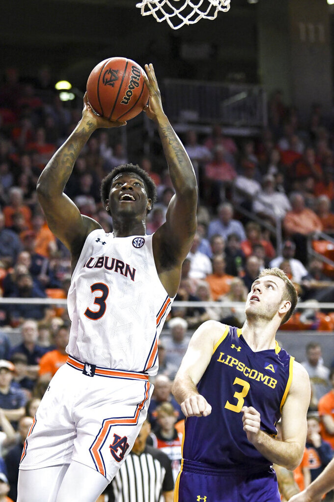 Auburn forward Danjel Purifoy (3) scores two points while defended by Lipscomb guard Michael Buckland (3) during the second half of an NCAA college basketball game Sunday, Dec. 29, 2019, in Auburn, Ala. (AP Photo/Julie Bennett)