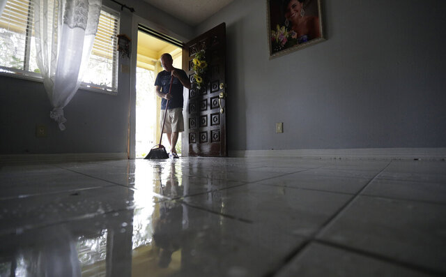 Martin Garcia sweeps water from his home, Monday, July 27, 2020, in Weslaco,Texas. The Garcia's home was flooded by Hurricane Hanna as it passed through the area dropping heavy rains which caused flooding. (AP Photo/Eric Gay)