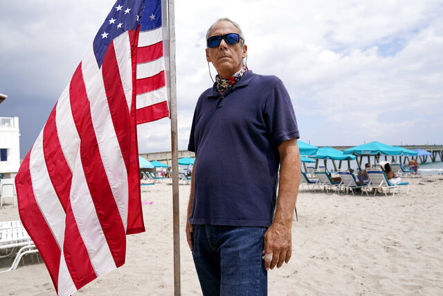 """Daniel Turner, a 59-year-old construction contractor, stands by a U.S. flag as he poses for a portrait, Saturday, Sept. 26, 2020, in Deerfield Beach, Fla. Turner had high hopes that Donald Trump's outsider status would help him cut through the bureaucracy in Washington. Then, the 2017 Charlottesville protest happened, with members of the alt right marching while a woman was killed. """"I probably say that the tipping point was definitely when he claimed there were good people on both sides in Charlottesville. I just don't know any good Nazis."""" (AP Photo/Lynne Sladky)"""