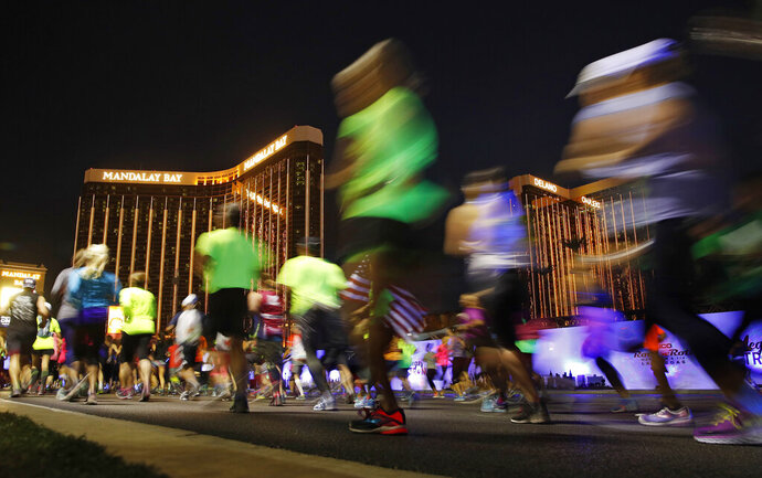 FILE - In this Nov. 12, 2017 file photo competitors run by Mandalay Bay, the site of the mass shooting at the Route 91 Harvest Festival during the Rock 'n' Roll Las Vegas Marathon along the Strip in Las Vegas. Tourism officials have approved a second, springtime Las Vegas marathon to run in the shadow of the glittering marquees of the resort-lined Strip. The Las Vegas Review-Journal reports the Las Vegas Convention and Visitors Authority on Tuesday, Nov, 12, 2019, authorized spending $150,000 to promote the race on the first Saturday in April, beginning in 2021. (AP Photo/John Locher,File)