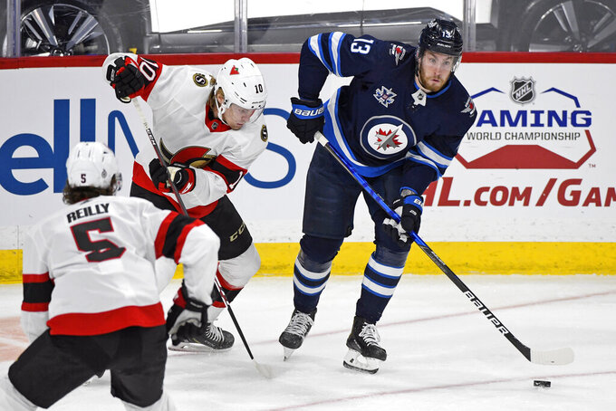 FILE - In this April 5, 2021, file photo, Winnipeg Jets' Pierre-Luc Dubois (13) looks to pass the puck past Ottawa Senators' Ryan Dzingel (10) during the first period of an NHL hockey game in Winnipeg, Manitoba. Dubois is looking forward to finally getting to know his Jets teammates after spending much of last season in Winnipeg isolated from them due to COVID-19 protocols coupled with a rash of injuries.(Fred Greenslade/The Canadian Press via AP, File)