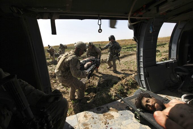 During a sporadic firefight, U.S. Army Staff Sgt. and flight medic Robert B. Cowdrey, of La Junta, Colo., top right, with Task Force Pegasus, coordinates a medical evacuation mission as Marine infantrymen carry onto a helicopter the second of two wounded Taliban fighters captured minutes earlier, according to witnesses, in Marjah, Helmand province, Afghanistan, Wednesday Feb. 17, 2010. (AP Photo/Brennan Linsley)