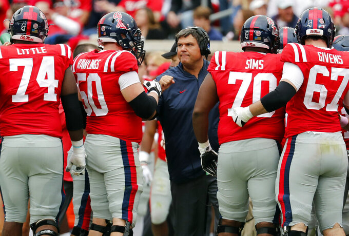 FILE  - In this Oct. 20, 2018, file photo, Mississippi coach Matt Luke speaks with his players during an NCAA college football game against Auburn in Oxford, Miss. Luke guided Mississippi's football program through the dark days of a two-year NCAA postseason ban. Now the Rebels believe the young coach--along with a few veteran coordinators--can push the program back in the Southeastern Conference's elite. The Rebels have remade their coaching staff over the winter, paying more than $7 million over the next three years to offensive coordinator Rich Rodriguez and defensive coordinator Mike MacIntyre. The well-respected duo has more than two decades of Division I head coaching experience between them. (AP Photo/Rogelio V. Solis, File)