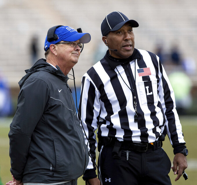 Duke head coach David Cutcliffe, left, and an official watch a replay on a video screen during an official review in the second half of an NCAA college football game against Wake Forest in Durham, N.C., Saturday, Nov. 24, 2018. The review indicated that Wake Forest successfully scored a touchdown on the previous play. (AP Photo/Ben McKeown)