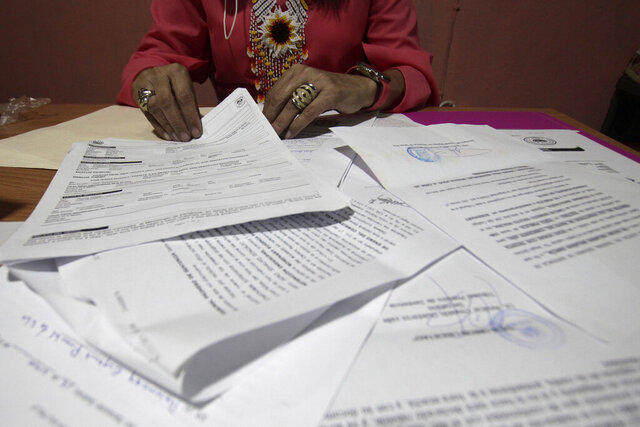 A Salvadoran businesswoman, who is one of the applicants of a small refugee program that was shut down by President Donald Trump, shows documents of the many times she has reported robberies and extortions, in Santa Ana, El Salvador, Saturday, Aug. 22, 2020. She said she was terrified when she began receiving death threats in 2013. Men with tattoos would come to a car wash she used to own to demand