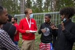 A Red Cross employee, center left, speaks to migrants at the newly built refugee camp in the Rudninkai military training ground, some 38km (23,6 miles) south from Vilnius, Lithuania, Wednesday, Aug. 4, 2021. The Red Cross warned Wednesday that Lithuania's decision to turn away immigrants attempting to cross in from neighboring Belarus does not comply with international law. Lithuania, a member of the European Union, has faced a surge of mostly Iraqi migrants in the past few months. Some 4,090 migrants, most of them from Iraq, have crossed this year from Belarus into Lithuania. (AP Photo/Mindaugas Kulbis)