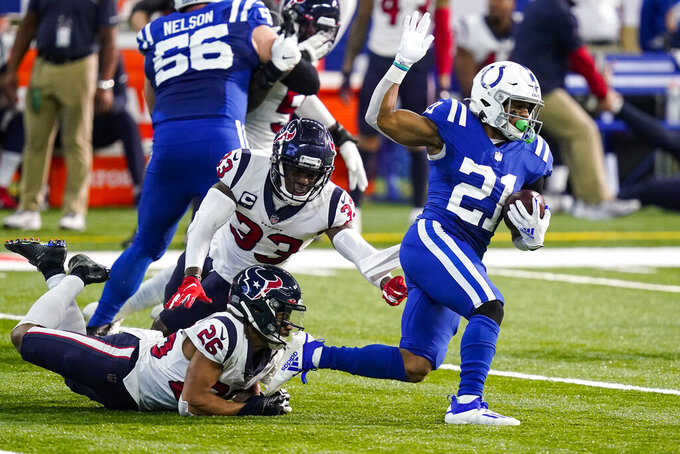 Indianapolis Colts running back Nyheim Hines (21) gets past Houston Texans safety A.J. Moore (33) and cornerback Vernon Hargreaves III (26) in the second half of an NFL football game in Indianapolis, Sunday, Dec. 20, 2020. (AP Photo/Darron Cummings)