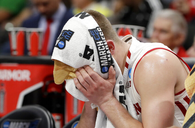 Wisconsin guard Brad Davison sits on the bench with a towel over his face during the second half of a first-round game against Oregon in the NCAA men's college basketball tournament Friday, March 22, 2019, in San Jose, Calif. (AP Photo/Chris Carlson)