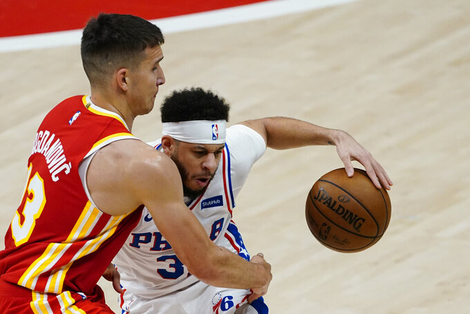 Philadelphia 76ers guard Seth Curry (31) tries to charge past Atlanta Hawks guard Bogdan Bogdanovic (13) during the first half of Game 3 of a second-round NBA basketball playoff series, Friday, June 11, 2021, in Atlanta. (AP Photo/John Bazemore)