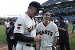 San Francisco Giants manager Bruce Bochy, left, laughs with former player Tim Lincecum during a ceremony honoring Bochy after a baseball game between the Giants and the Los Angeles Dodgers in San Francisco, Sunday, Sept. 29, 2019. (AP Photo/Jeff Chiu, Pool)