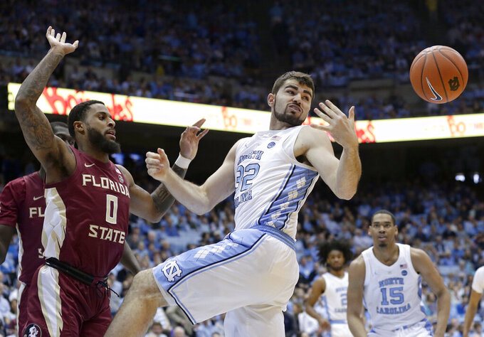 North Carolina's Luke Maye (32) reaches for a rebound with Florida State's Phil Cofer (0) during the first half of an NCAA college basketball game in Chapel Hill, N.C., Saturday, Feb. 23, 2019. (AP Photo/Gerry Broome)