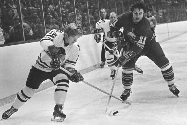 FILE - In this Dec. 15, 1971, file photo, Chicago Blackhawks' Pat Stapleton (12) battles for the puck with Buffalo Sabres' Gilbert Perreault  (11) during an NHL hockey game at Chicago. Stapleton, a longtime NHL defenseman who famously kept an air of mystery over whether he possessed the puck from the winning goal of the 1972 Summit Series, died Wednesday night, April 8, 2020. He was 79.  (AP Photo/Fred Jewell, File)