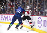 FILE - Vancouver Canucks' Tyler Myers, left, checks New Jersey Devils' Jack Hughes during the third period of an NHL hockey game in Vancouver, British Columbia, in this Sunday, Nov. 10, 2019, file photo. The No. 1 overall pick in 2019 draft had a tough rookie season. He finished with seven goals and 14 assists and was a minus 26.  Hughes has immense talent and he created a lot of opportunities for himself and his linemates. He just didn't find the net. His other problem was he was teen-ager playing with men. They knocked him down repeatedly. (Darryl Dyck/The Canadian Press via AP, File)