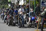 Motorcyclists wearing masks amid the new coronavirus wait their turn to fill up at a gas station in Caracas, Venezuela, Monday, June 1, 2020. Starting Monday, Venezuelans pay international market fuel prices, with limited access to subsidized gasoline each month, marking a historic break in the country's practice of having the world's cheapest fuel. (AP Photo/Ariana Cubillos)