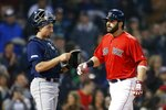 Boston Red Sox's Mitch Moreland, right, crosses home plate on his three-run home run in front of Seattle Mariners' Tom Murphy during the third inning of a baseball game in Boston, Friday, May 10, 2019. (AP Photo/Michael Dwyer)