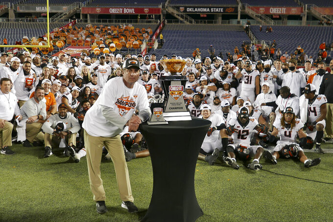 Oklahoma State head coach Mike Gundy poses with the Championship trophy and his team after winning the Cheez-it Bowl NCAA college football game against the Miami, Tuesday, Dec. 29, 2020, in Orlando, Fla. (AP Photo/John Raoux)