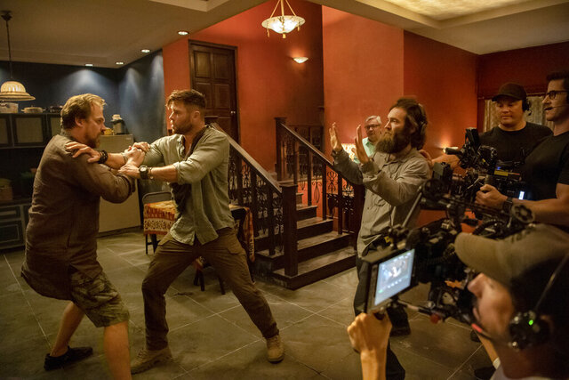 This image released by Netflix shows actors David Harbour, from left, and Chris Hemsworth being directed by Sam Hargrave for a scene in the action film
