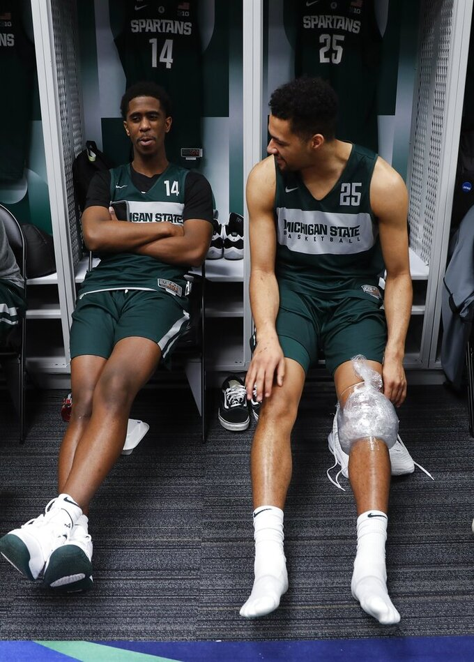 Brock Washington (14) talks to Kenny Goins after a practice session for the semifinals of the Final Four NCAA college basketball tournament, Thursday, April 4, 2019, in Minneapolis. (AP Photo/Jeff Roberson)