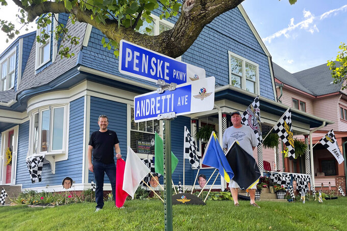 Chris Otto, left, of Seattle, and his brother Eric Otto, pose outside Eric's home, decorated for the Spectacle of Homes contest to be featured ahead of the Indianapolis 500 auto race, Thursday, May 27, 2021, in Indianapolis. Because the traditional parade has been canceled because of the coronavirus pandemic, drivers will instead cruise by homes that have been decorated to celebrate the 105th running of the race. (AP Photo/Jenna Fryer)