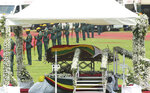 The casket carrying the remains of the former president Robert Mugabe displayed on a a podium at the National Sports stadium during a funeral procession in Harare, Saturday, Sept, 14, 2019. African heads of state and envoys are gathering to attend a state funeral for Mugabe, whose burial has been delayed for at least a month until a special mausoleum can be built for his remains. (AP Photo/Tsvangirayi Mukwazhi)