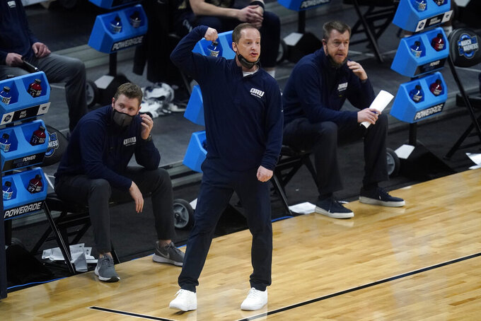 Oral Roberts head coach Paul Mills watches from the bench during the first half of a Sweet 16 game against Arkansas in the NCAA men's college basketball tournament at Bankers Life Fieldhouse, Saturday, March 27, 2021, in Indianapolis. (AP Photo/Darron Cummings)