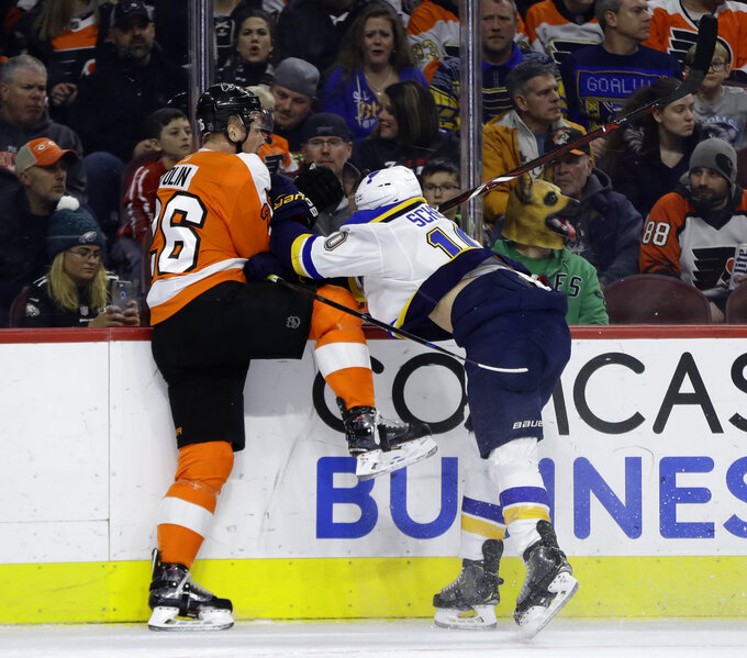 St. Louis Blues' Brayden Schenn, right, checks Philadelphia Flyers' Christian Folin into the boards during the first period of an NHL hockey game, Monday, Jan. 7, 2019, in Philadelphia. (AP Photo/Matt Slocum)