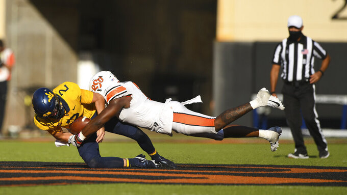 Oklahoma State linebacker Amen Ogbongbemiga (7) tackles West Virginia quarterback Jarret Doege (2) during an NCAA college football game Saturday, Sept. 26, 2020, in Stillwater, Okla. (AP Photo/Brody Schmidt)