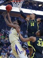 Washington's Noah Dickerson shoots around Oregon's Kenny Wooten (14) and Francis Okoro during the first half of an NCAA college basketball game in the final of the Pac-12 men's tournament Saturday, March 16, 2019, in Las Vegas. (AP Photo/John Locher)