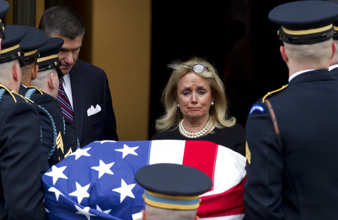 Rep. Debbie Dingell, D-Mich., watches the flag-draped casket of former Rep. John Dingell upon arrival at Holy Trinity Catholic Church for a funeral service, Thursday, Feb. 14, 2019, in Washington. Dingell, the longest-serving member of Congress in American history who mastered legislative deal-making and was fiercely protective of Detroit's auto industry, has died at age 92. (AP Photo/Jose Luis Magana)
