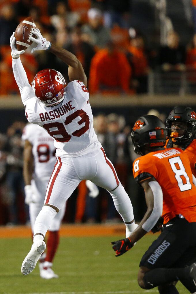 Oklahoma wide receiver Nick Basquine (83) jumps up to catch a pass in front of Oklahoma State cornerback Rodarius Williams (8) in the first half of an NCAA college football game in Stillwater, Okla., Saturday, Nov. 30, 2019. (AP Photo/Sue Ogrocki)