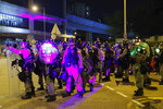 Riot police are illuminated by laser pointers from protesters during a protest at the Yuen Long MTR station in Hong Kong, Wednesday, Aug. 21, 2019. Hong Kong riot police faced off with protesters occupying a suburban train station Wednesday evening following a commemoration of a violent attack there by masked assailants on supporters of the anti-government movement. (AP Photo/Kin Cheung)