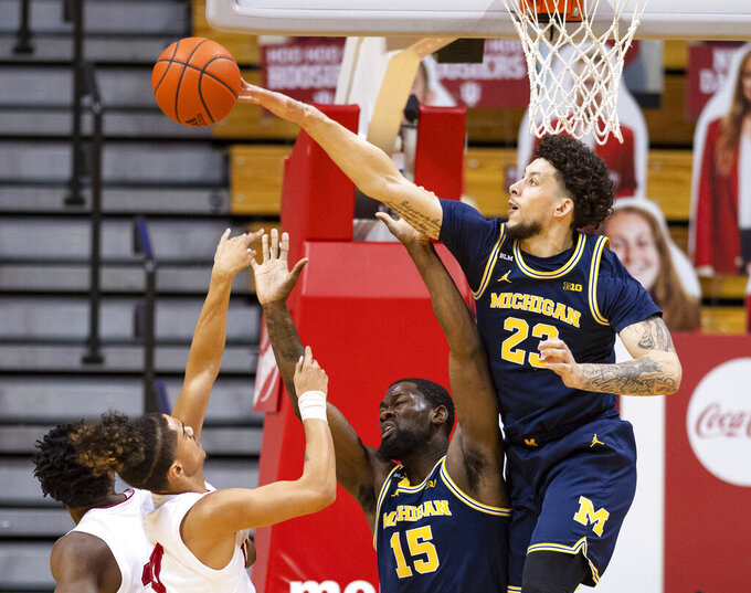 Michigan forward Brandon Johns Jr. (23) blocks a shot by Indiana guard Khristian Lander (4) during the first half of an NCAA college basketball game, Saturday, Feb. 27, 2021, in Bloomington, Ind. (AP Photo/Doug McSchooler)