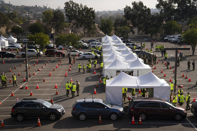 Motorists wait to get their COVID-19 vaccine at a federally-run vaccination site set up on the campus of California State University of Los Angeles in Los Angeles, Calif., Tuesday, Feb. 16, 2021. (AP Photo/Jae C. Hong)