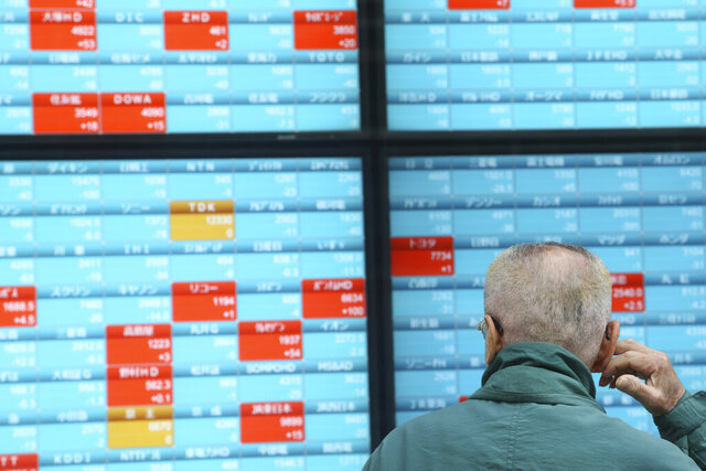 A man looks at an electronic stock board of a securities firm in Tokyo, Monday, Dec. 30, 2019. Asian shares were mostly lower Monday as investors awaited updates on the signing of a trade deal between the U.S. and China and kept a wary eye on North Korea.  (AP Photo/Koji Sasahara)