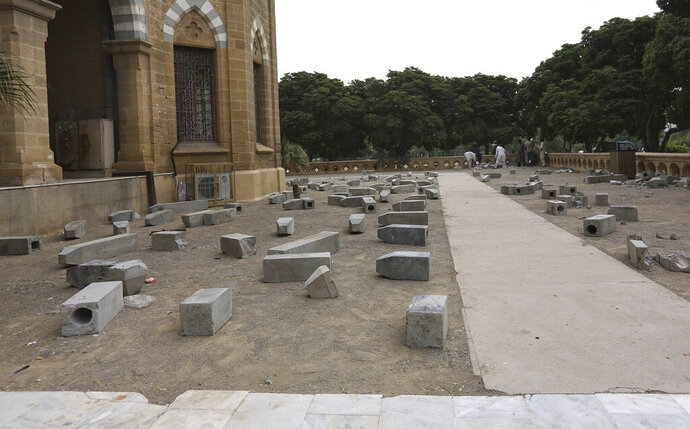 Workers of Karachi Municipal Corporation remove an artwork of concrete tombstones marking the number of