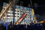 In this photo taken Monday, Jan. 13, 2020, a bus that tipped into a chasm is lifted up as rescue workers look for victims in Xining in northwestern China's Qinghai province. The bus plunged through a collapsed section of road in northwestern China, killing some and leaving others missing, authorities said. (Ma Minyan/cnsphoto via AP)