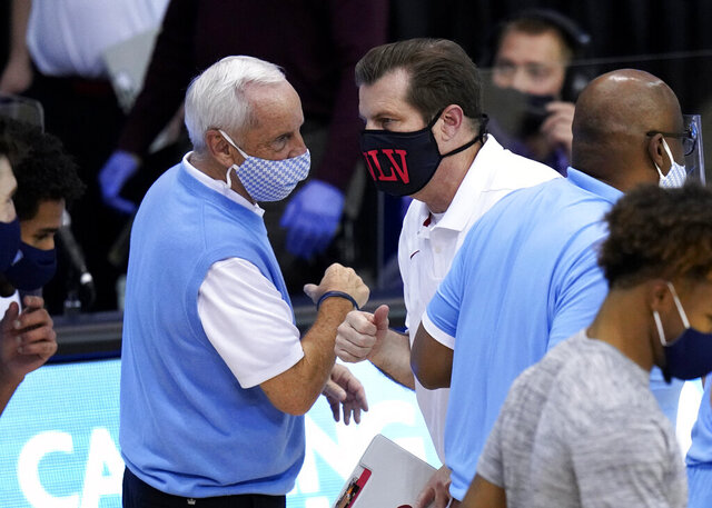 North Carolina head coach Roy Williams bumps-fists and talks with UNLV head coach T.J. Otzelberger after an NCAA college basketball game in the Maui Invitational tournament, Monday, Nov. 30, 2020, in Asheville, N.C. (AP Photo/Kathy Kmonicek)