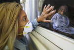 Camilla White visits her mother Lillian Barber, 90, from outside, seeing her through the window while touching fingertips through the glass at Cottage Landing Assisted Living on Tuesday, April 28, 2020, in Carrollton, Ga. White didn't discover there had been several deaths at the home from coronavirus and a significant outbreak until seeing the info on a state website and said that before the outbreak