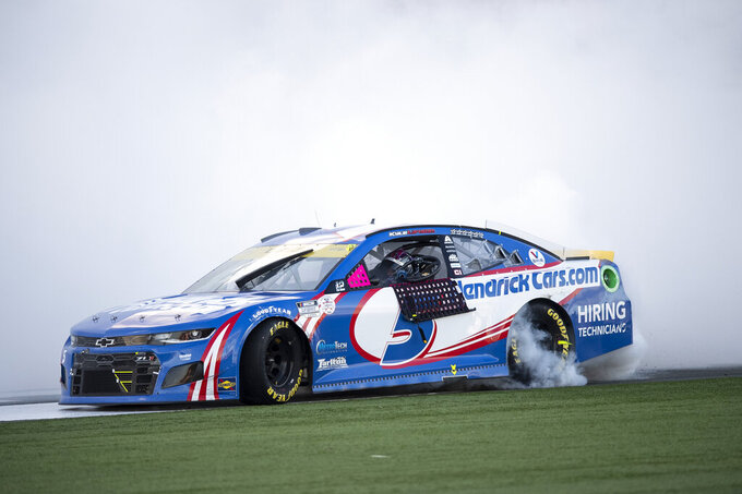 Kyle Larson (5) celebrates with a burnout after winning a NASCAR Cup Series auto racing race at Charlotte Motor Speedway, Sunday, Oct. 10, 2021, in Concord, N.C. (AP Photo/Matt Kelley)