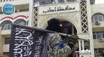 FILE - In this file photo posted on the Twitter page of Syria's al-Qaida-linked Nusra Front on March 28, 2015, a fighter from Syria's al-Qaida-linked Nusra Front holds his group flag as he stands in front of the governor building in Idlib province, north Syria. n two months of intensive airstrikes and bombardments on the rebel-controlled province of Idlib, Syrian government forces and their Russian allies have failed to make progress against battle-hardened insurgents. (Al-Nusra Front Twitter page via AP, File)