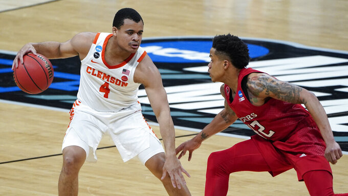 Clemson guard Nick Honor (4) protects the ball from Rutgers guard Jacob Young (42) during the first half of a men's college basketball game in the first round of the NCAA tournament at Bankers Life Fieldhouse in Indianapolis, Friday, March 19, 2021. (AP Photo/Paul Sancya)