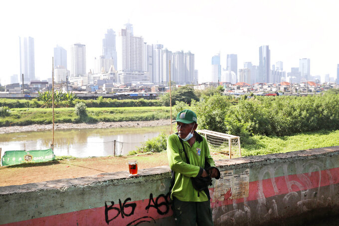 A municipal worker takes a break as the hazy city skyline is seen in the background in Jakarta, Indonesia, Thursday, Sept. 16, 2021. An Indonesian court ruled Thursday that President Joko Widodo and six other top officials have neglected to fulfill citizens' rights to clean air and ordered them to improve the poor air quality in the capital. (AP Photo/Tatan Syuflana)