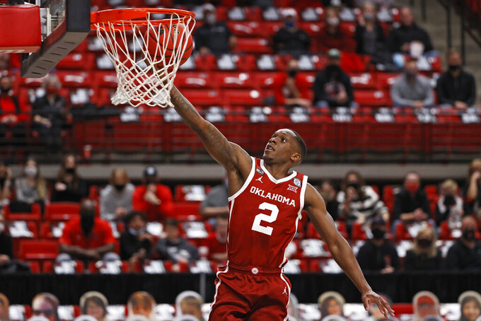 Oklahoma's Umoja Gibson (2) lays up the ball during the first half of an NCAA college basketball game against Texas Tech, Monday, Feb. 1, 2021, in Lubbock, Texas. (AP Photo/Brad Tollefson)
