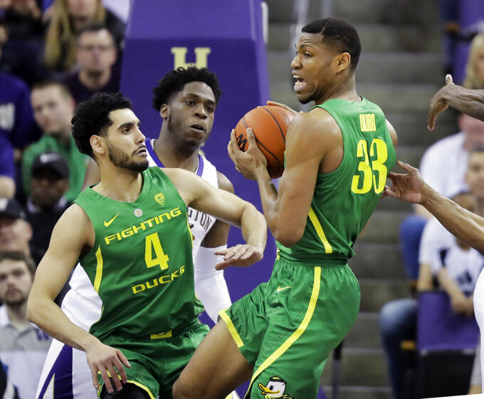 Oregon forward Francis Okoro (33) pulls down a rebound in front of Washington forward Noah Dickerson, second from left, and Oregon guard Ehab Amin (4), during the first half of an NCAA college basketball game, Saturday, March 9, 2019, in Seattle. (AP Photo/Ted S. Warren)