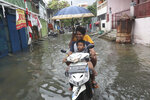 Residents ride a motorbike on a flooded street in Jakarta, Indonesia, Sunday, Jan. 5, 2020. Landslides and floods triggered by torrential downpours have left dozens of people dead in and around Indonesia's capital, as rescuers struggled to search for people apparently buried under tons of mud, officials said Saturday. (AP Photo/Tatan Syuflana)