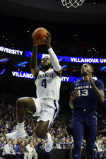 Villanova's Eric Paschall (4) goes up for a shot past Xavier's Naji Marshall (13) during the first half of an NCAA college basketball game Friday, Jan. 18, 2019, in Philadelphia. (AP Photo/Matt Slocum)