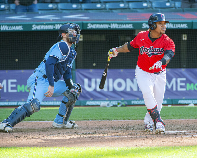 Cleveland Indians' Jose Ramirez along with Toronto Blue Jays' Danny Jansen watch his game winning sacrifice fly off Anthony Castro during the seventh inning of the second baseball game of a doubleheader in Cleveland, Sunday, May 30, 2021. (AP Photo/Phil Long)