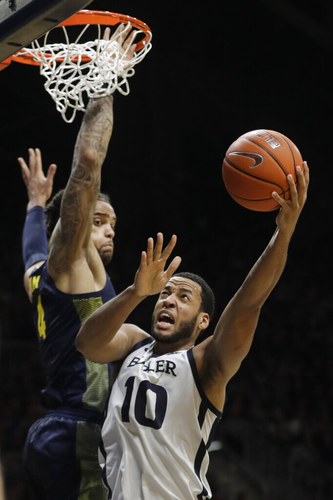 Butler's Bryce Nze (10) shoots against Marquette's Theo John (4) during the first half of an NCAA college basketball game, Friday, Jan. 24, 2020, in Indianapolis. (AP Photo/Darron Cummings)