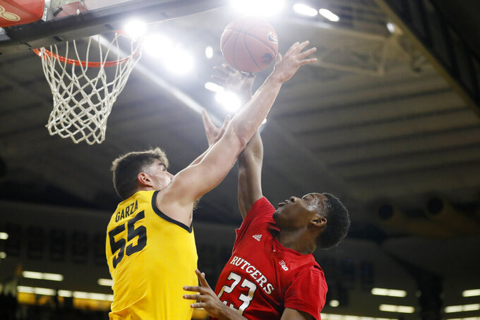 Rutgers guard Montez Mathis (23) is fouled by Iowa center Luka Garza (55) while driving to the basket during the first half of an NCAA college basketball game, Wednesday, Jan. 22, 2020, in Iowa City, Iowa. (AP Photo/Charlie Neibergall)